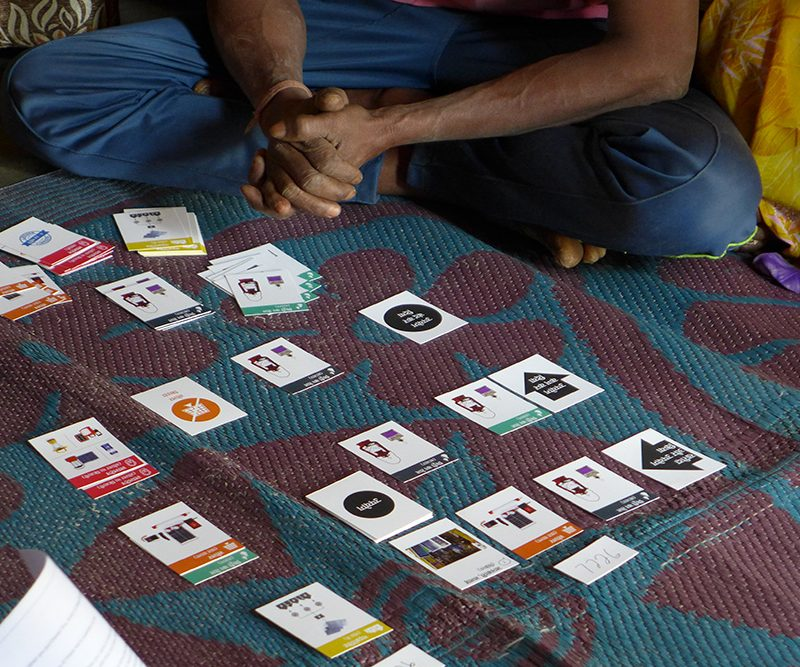 When interviewing a household, the researchers use cards representing various devices, the local microgrid, and the state-run electricity grid. Members of the household together recall the order in which they acquired their energy sources and lay down cards accordingly. At each decision point, the researchers ask why they made that choice. Credit: Ameya Athavankar